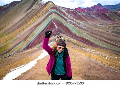 Young woman celebrating with the fist held high, after a long tracking through Vinicunca (rainbow mountain) Perú.