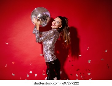 Young woman  celebrating on a red background