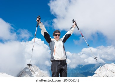 Young woman celebrating on top of a mountain after successful ascend