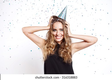 Young woman in a celebratory cap fooling around at a party on the background of falling confetti