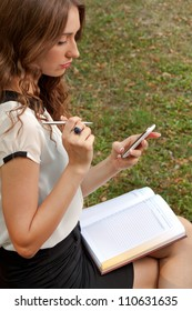 Young woman with a cell phone and notebook in park