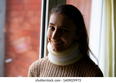 Young woman with a cervical collar smiling. Neck brace and traffic accident Concept.