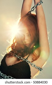 Young woman with chain portrait. Bright flash on background.