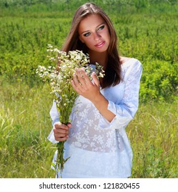 Young woman with chamomile bouquet