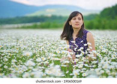 Young woman in chamomile meadow. Nature composition.
