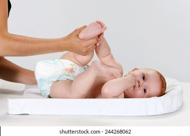 Young woman changing a baby's diaper