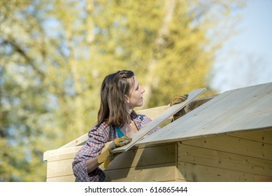 Young woman in check shirt putting a wooden plank on roof of garden shed (hut or summerhouse), a do-it-yourself construction, background of trees.