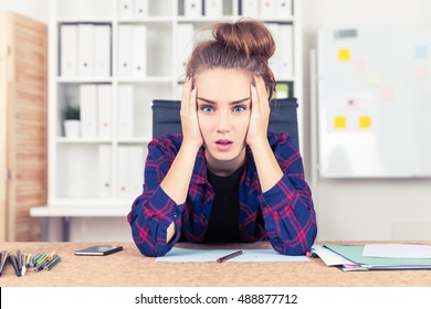 Young woman in checkered shirt is overwhelmed with amount of work she is supposed to do. Concept of overworking