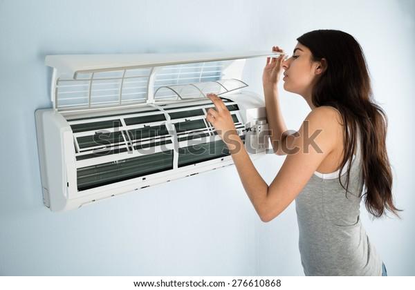 家の中のエアコンをチェックする若い女性