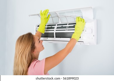 Young Woman Checking And Cleaning Air Conditioning System At Home