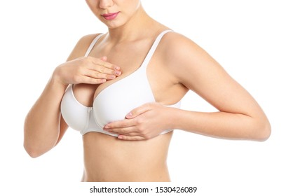 Young woman checking her breast on white background. Cancer awareness concept