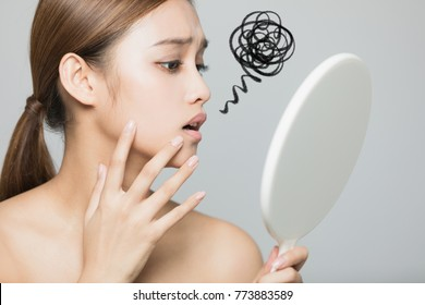 Young woman checking her skin. Skin care concept.