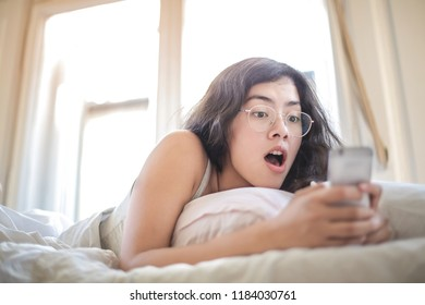 Young woman checking her smartphone in bed.