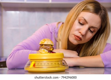 Young woman checking how many calories does mini burger have , diet concept
