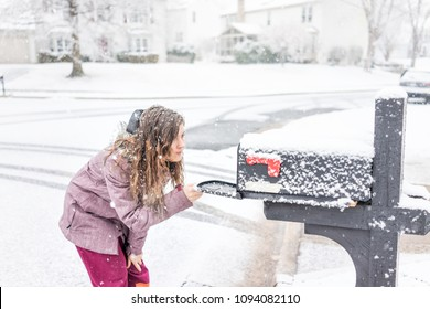 Young woman checking mail in neighborhood road with snow covered ground during blizzard white storm, snowflakes falling in Virginia suburbs, single family homes in mailbox box