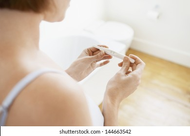 Young woman checking pregnancy test kit in bathroom
