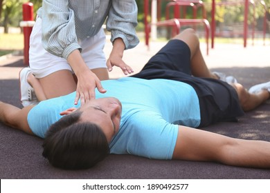 Young woman checking pulse of unconscious man outdoors. First aid