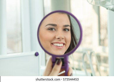 Young woman checking their teeth at mirror after dental treatment - People bodycare and stomatology concept for healthy lifestyle - Focus on girl face
