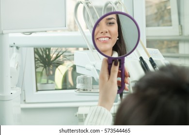 Young woman checking their teeth at mirror after dental treatment - People bodycare and stomatology concept for healthy lifestyle - Focus on girl face -