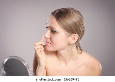 Young woman checks her nose in the mirror