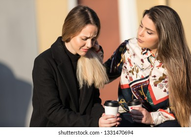 Young woman cheering up crying female friend at the street with unfocused background