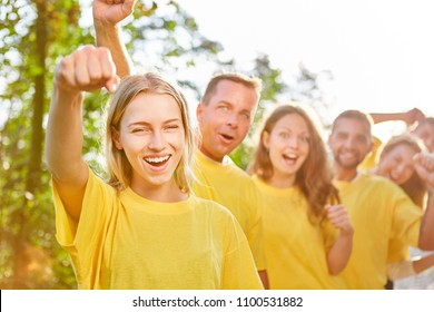 Young woman cheers and rejoices with her team at a teambuilding workshop