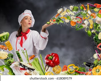 Young woman chef blowing fresh vegetable in water splashes. Concept of food preparation