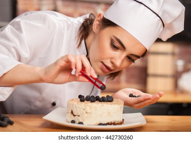young woman chef cook preparing a sweet cake in the kitchen, putting blueberries on it