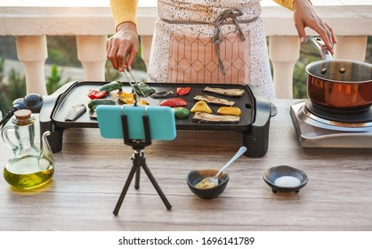 Young woman chef cooking outdoor while streaming online for webinar masterclass lesson at home - Female making videos preparing vegetarian meal on patio terrace - Food concept - Focus on hands