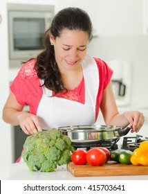 Young woman chef cooking with skeptical facial expressions, interacting frustrated body language