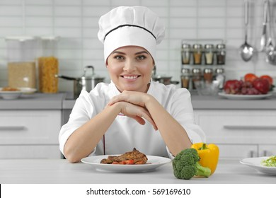 Young woman chef with prepared meat dish on plate