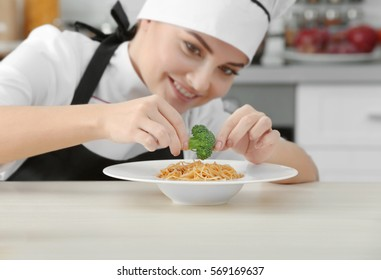Young woman chef putting broccoli on plate with pasta