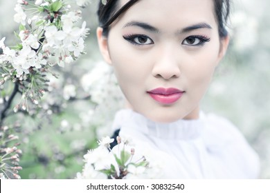 Young woman with cherry flowers. Shallow dof effect.