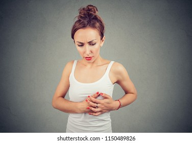 Young woman with chest breast pain palpating a lump isolated on gray background