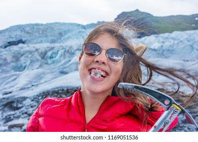 Young woman chewing glacial ice and holding an ice axe on a blue ice tour on the amazing Vatnajokull glacier in South Iceland