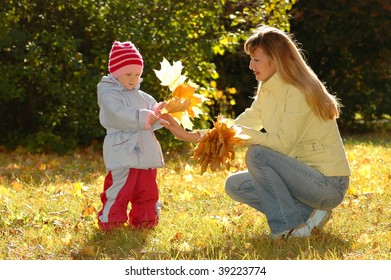 Young woman and child collect autumn sheets in park