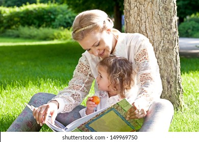 Young woman with child (daughter) in park read book