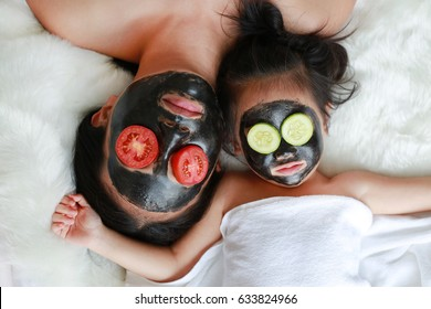 Young woman and child girl in black peeling face mask, beauty concept.