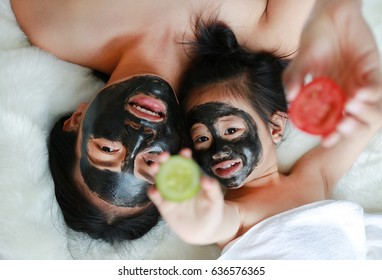 Young woman and child girl in coal peeling face mask holding tomato and cucumber slices on hands, beauty concept.