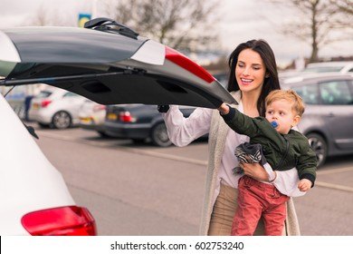 young woman  with a child in her arms, closing the luggage in the car, standing near gray car. After shopping luggage with products