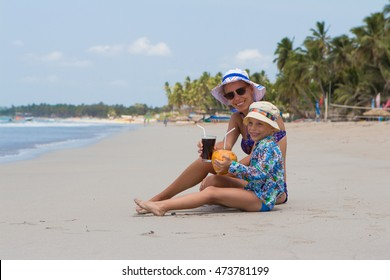 Young woman and child on the beach drinking cocktails