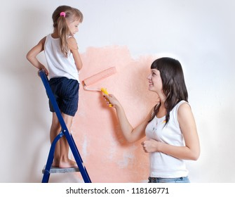 Young woman and child painting the walls, repair