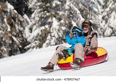 Young woman and child sliding down in inflatable snow tube