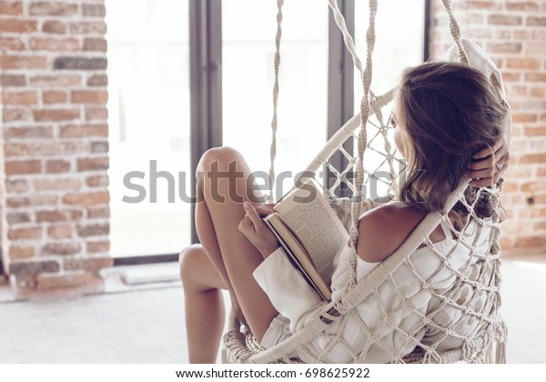 Mujer joven relajándose en casa en una cómoda silla colgante. Chica relajante y leyendo un libro en columpio en sala de estar con paredes de ladrillo.