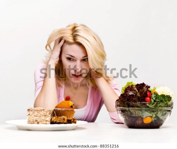 Young woman chooses between  a salad and baking