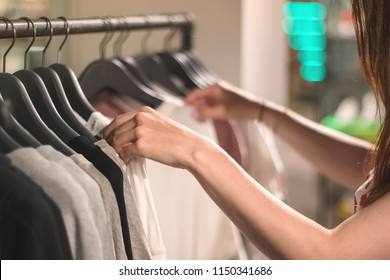 A young woman chooses clothes on hangers in the shop, store, boutique, showroom or shopping mall. Pastel colors. Close up with blurred background