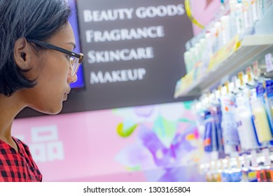A young woman chooses cosmetics at a store. Asian girl purchases drugstore at a supermarket. Buying cosmetics in a Japanese shop.