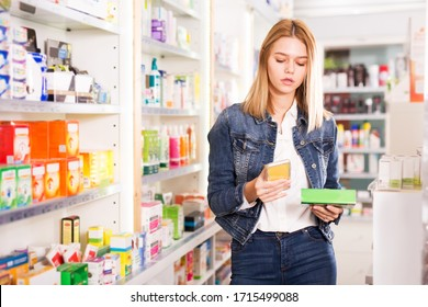 Young woman chooses medicine in a pharmacy and writes a message on the phone