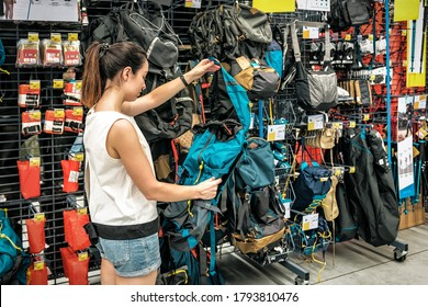 Young woman chooses a new backpack in a travel store. Sport supermarket