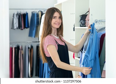 Young woman chooses new clothes in the store. Seller in the store hangs the dress on the hangers. Small business, selling clothes.